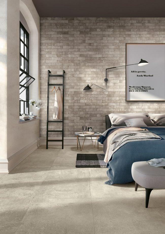 décoration d une chambre style industriel avec un carrelage effet béton au sol et un parement brique au mur pour un style indus dans une maison rénovée de saint aunes