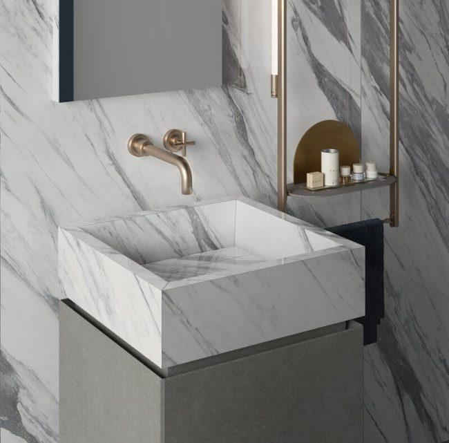 meuble salle de bain vasque a poser sur rangement en grès cérame effet marbre pour un style art déco dans une maison a saint Clément de rivière